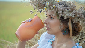 Young beautiful girl is drinking milk from a jug on the nature Stock Photo