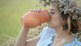 Young beautiful girl is drinking milk from a jug on the nature Royalty Free Stock Photos