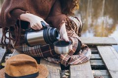 Girl drinking tea on a wooden bridge on a lake. Young beautiful girl drinking tea on a wooden old bridge on a lake in the picturesque autumn forest. Toning Stock Images