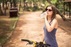 A young beautiful girl drinking water from a bottle. Stock Photos