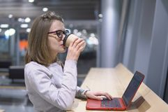 Young, beautiful girl drinks coffee standing at the table with laptop at the airport Royalty Free Stock Photos