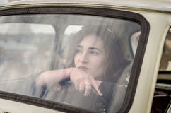 Young beautiful girl driving an old vintage car.  royalty free stock photo