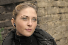 Young beautiful girl with earbud. Royalty Free Stock Images