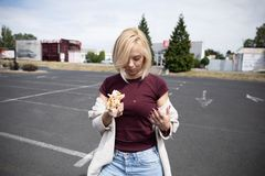 A young woman holds a bitten hot dog royalty free stock photography