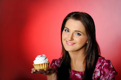 Young beautiful girl eating small sweet cake Royalty Free Stock Images