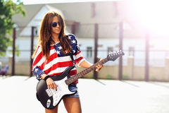 Young beautiful girl with electric guitar. Outdoor fashion portr. Ait Royalty Free Stock Photo
