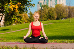 Young beautiful girl is engaged in yoga, outdoors in a park Royalty Free Stock Images