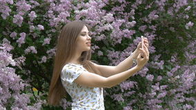 A young beautiful girl is enjoying a beautiful lilac bush. Makes a selfie on a smartphone. Summer day, good mood. stock video