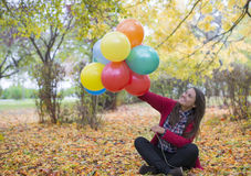 Young and beautiful girl enjoying her ballons. Young and beautiful woman enjoying her colored balloons royalty free stock photo