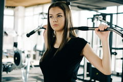 Young beautiful girl exercising in the fitness gym, with lat machine Royalty Free Stock Photography