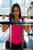 Young beautiful girl exercising in the fitness gym, with lat machine Royalty Free Stock Photos