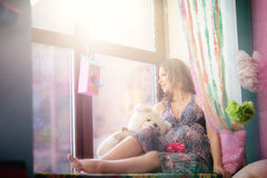 A young, beautiful girl, the expectant mother sits on a window s stock photos