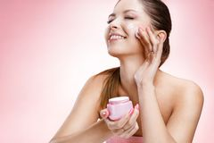 Young beautiful girl with a face cream Stock Photography