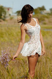 Young beautiful girl in a field with flowers in white sundress Royalty Free Stock Photo