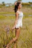 Young beautiful girl in a field with flowers in white sundress Royalty Free Stock Image