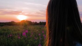 Young beautiful girl in the field looks at the setting sun. Close Up Shot. Slow Motion. Young beautiful girl in the field looks at the setting sun. Close Up Shot stock video