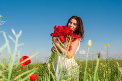 Young beautiful girl in the field with a poppies bouquet. Royalty Free Stock Photo