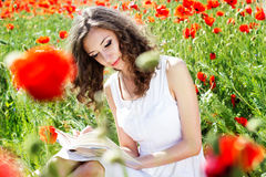 Young beautiful girl in the field of poppies Stock Photo