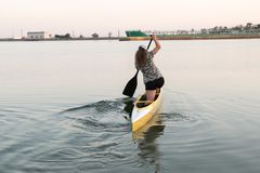 Young beautiful girl is floating on a reservoir in a canoe. The concept of sport and a healthy lifestyle.  Royalty Free Stock Image