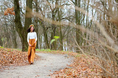 Young beautiful girl with flower wreath outdoors in the autumn forest Royalty Free Stock Photos