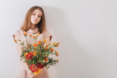 Young beautiful girl with flowers on background  wall Stock Images
