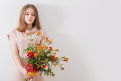 Young beautiful girl with flowers on background white wall Stock Image