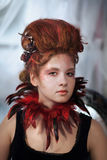 Young beautiful girl in the form of the evil fairy. With red hair in a designer dress with a long skirt in unusual shoes and a necklace of feathers Stock Image