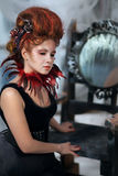 Young beautiful girl in the form of the evil fairy. With red hair in a designer dress with a long skirt in unusual shoes and a necklace of feathers stock photography