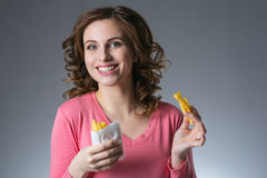 Young beautiful girl with a French fries from a fast food smilin. G on a gray background Stock Photography