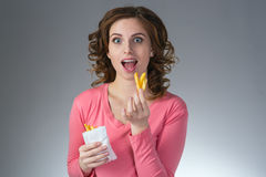 Young beautiful girl with a French fries from a fast food smilin Royalty Free Stock Images