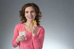 Young beautiful girl with a French fries from a fast food smilin. G on a gray background Royalty Free Stock Images