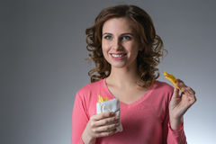 Young beautiful girl with a French fries from a fast food smilin. G on a gray background Stock Images