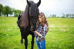 Young beautiful girl with frisian horse. Standing in the meadow at summer time Royalty Free Stock Photography