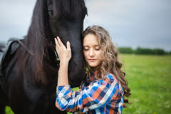 Young beautiful girl with frisian horse Stock Photos