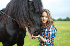 Young beautiful girl with frisian horse Royalty Free Stock Images