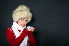 The young beautiful girl in a fur cap has control Stock Photography