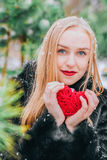Young beautiful girl in fur coat standing in the snowy woods and keeps braided red heart. The effect of retro, grain Stock Image