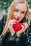 Young beautiful girl in fur coat standing in the snowy woods and keeps braided red heart. The effect of retro, grain Royalty Free Stock Photos