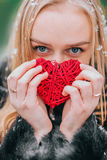 Young beautiful girl in fur coat standing in the snowy woods and keeps braided red heart. The effect of retro, grain Royalty Free Stock Photography