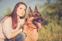 Young beautiful girl with a German shepherd playing on the lawn Royalty Free Stock Images