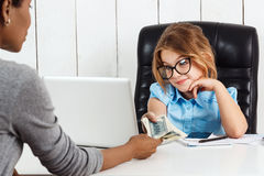Young beautiful girl getting money at working place in office. Stock Photography
