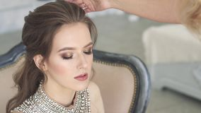 Young beautiful girl getting ready for evening party. Charming brunette doing makeup stock footage