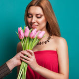 Young beautiful girl gives a bouquet of tulips man Royalty Free Stock Image