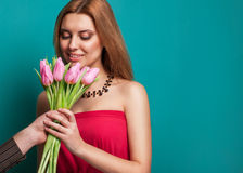 Young beautiful girl gives a bouquet of tulips man Stock Photos