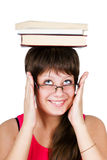 Young beautiful girl in glasses with books on head. isolated on Royalty Free Stock Images