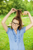 Young beautiful girl glasses combs hair Stock Image