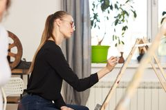 Young beautiful girl in glasses dressed in black blouse and jeans sits at the easel and paints a picture in the drawing stock photo