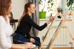 Young beautiful girl in glasses dressed in black blouse and jeans sits at the easel and paints a picture in the drawing royalty free stock photo