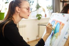 Young beautiful girl in glasses dressed in black blouse sits at the easel and paints a picture in the drawing school stock images