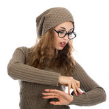 Young beautiful girl with glasses looking at his watch. Royalty Free Stock Photography
